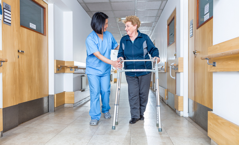 Older woman using a walker with a therapist in rehab facility