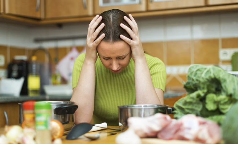Woman trying to cook holding head with head and cervical spine injuries
